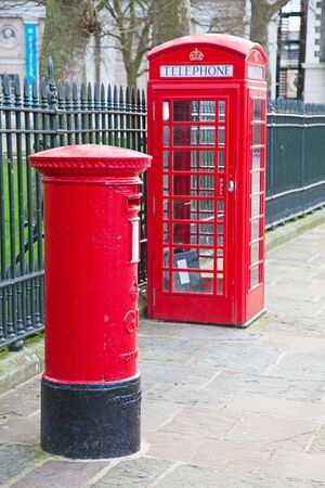 red post box: Famous red post box and telephone booth in London, UK Stock Photo