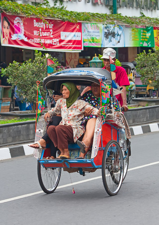 YOGYAKARTA - AUGUST 03: Traditional rikshaw transport on streets of Yogyakarta, Java, Indonesia on August 03, 2010. Bicycle rikshaw remains popular means of transport in many Indonesian cities. Фото со стока - 54685473