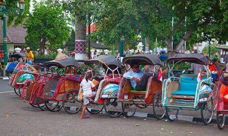 transportation travel: YOGYAKARTA - AUGUST 03: Traditional rikshaw transport on streets of Yogyakarta, Java, Indonesia on August 03, 2010. Bicycle rikshaw remains popular means of transport in many Indonesian cities.