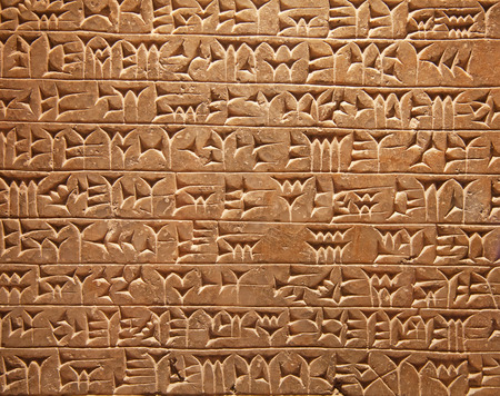 Ancient sumerian stone carving with cuneiform scripting Фото со стока