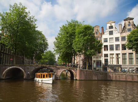 AMSTERDAM - JULY 10: Canals of the Amsterdam city on July 10, 2016 in Amsterdam, Netherlands. The historical canals of the city surrounded by traditional dutch houses is one of the main attractions of Amsterdam. Editorial