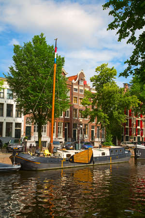 retailers: AMSTERDAM - JULY 10: Canals of the Amsterdam city on July 10, 2016 in Amsterdam, Netherlands. The historical canals of the city surrounded by traditional dutch houses is one of the main attractions of Amsterdam. Editorial