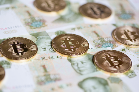 Bitcoins over the background made of Chinese yuan