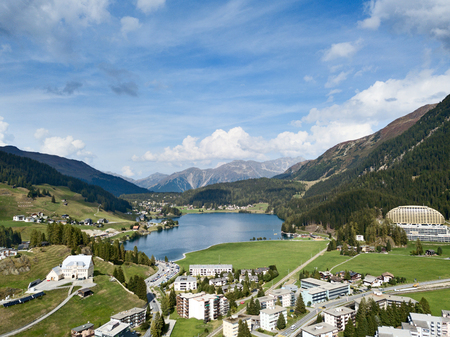 Aerial view of Davos city and lake. Davos is swiss city, famous location of annual meetings of World Economic Forum. Фото со стока
