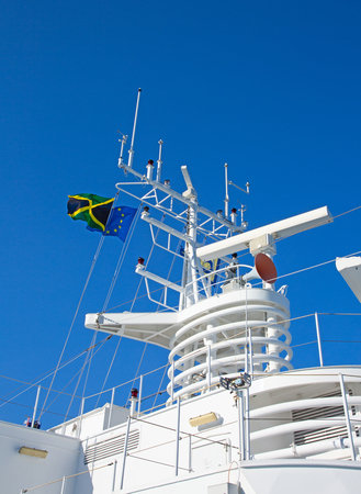 Navigation equipment and masts of cruise ship decorated with flags Standard-Bild - 119246596