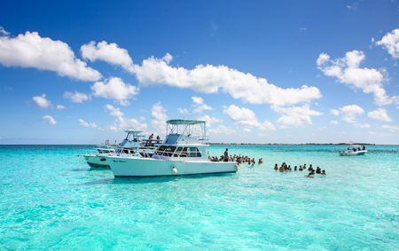 GEORGE TOWN - February 16: Unidentified people visiting Stingray city on Gran Cayman on February 16, 2019 in George town, Cayman islands. Stigray city is famous snokerling spot visited on cruise in Caribbean sea. Editorial