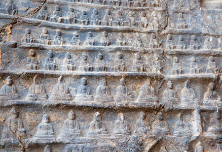 Famous Longmen Grottoes (statues of Buddha and Bodhisattvas carved in the monolith rock near Luoyang in Hennn province, China) 免版税图像 - 120289009