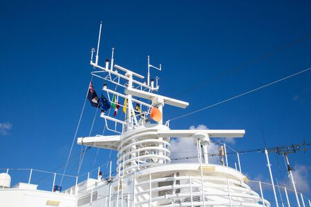 Navigation equipment and masts of cruise ship decorated with flags Stok Fotoğraf - 132114838
