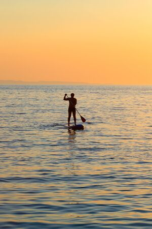 Stand up paddling in the open sea at sunset