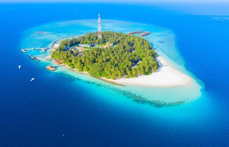 Small island in the Maldives covered by palms and surrounded by turquoise blue waters with with beautiful corals and animals, perfect escape from the cold winter Stock Photo