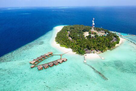 Petite île des Maldives couverte de palmiers et entourée d'eaux bleu turquoise avec de beaux coraux et animaux, parfaite évasion du froid hivernal