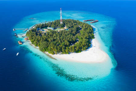 Small island in the Maldives covered by palms and surrounded by turquoise blue waters with with beautiful corals and animals, perfect escape from the cold winter