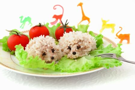 groat: Food for children, two funny rice hedgehogs, tomatoes, salad and toys on the white background Stock Photo