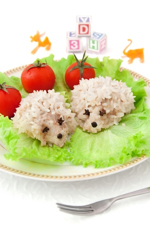 Food for children, two funny rice hedgehogs, tomatoes, salad and toys on the white background photo