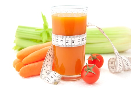 tapeline: Glass of vegetable juice with tape measure and fresh vegetables on white background