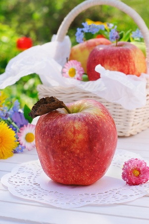 Red apple, flowers and basket on white garden table in sunny summer day photo