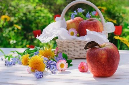 Manzanas rojas, flores y cesta de tabla jardín blanco en día soleado de verano Foto de archivo