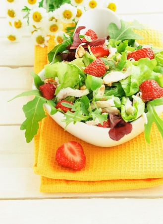 Green salad with strawberry, chicken, nuts, cheese in a white bowl on the table photo
