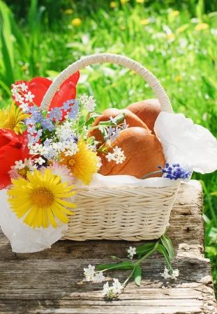 Witte mand met pasteitjes en heldere bloemen op oude tafel in de tuin in de zomer dag