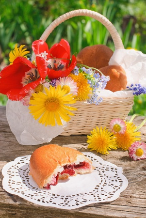 Bitten off a cherry pie and basket with flowers on the old table in the garden in summer day photo