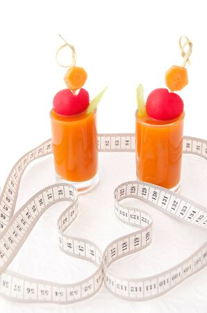 Vegetable juice in two short glasses with tape measure photo