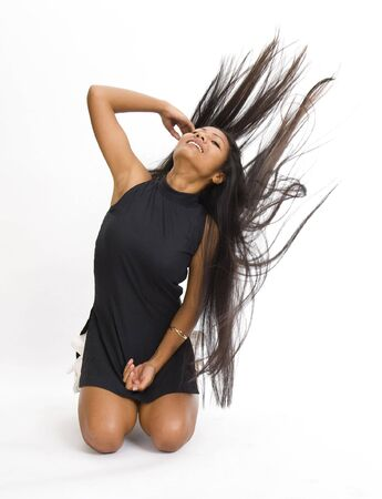 young asian woman pulls her very long hair back over her shoulder photo