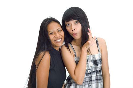 Two young asian women making fun of someone photo