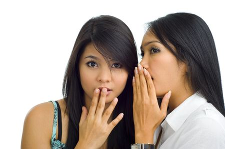 two young asian girlfriends gossip, isolated on white