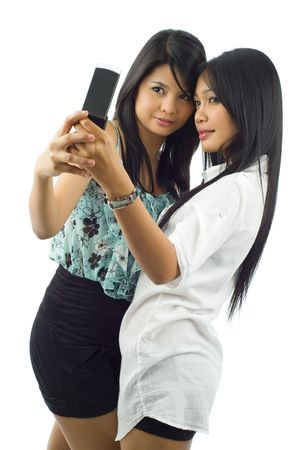 two asian women taking a picture of themselves with a mobile phone, isolated on white Stock Photo - 5060090
