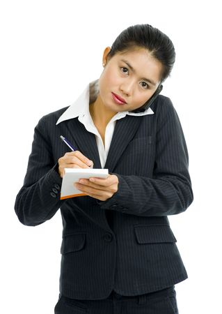 beautiful young asian businesswoman on the phone taking notes, isolated on white Stock Photo - 5143906