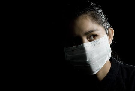 flu alarm: protective face mask on beautiful asian woman. low-key picture. photo