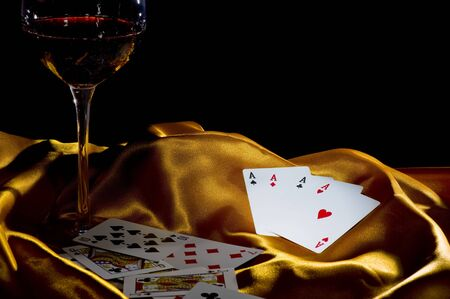 poker ace and a glass of wine on a golden silk. low key shot with focus on the 4  photo