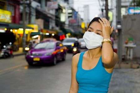 antiviral: young asian woman with face mask in the streets of bangkok