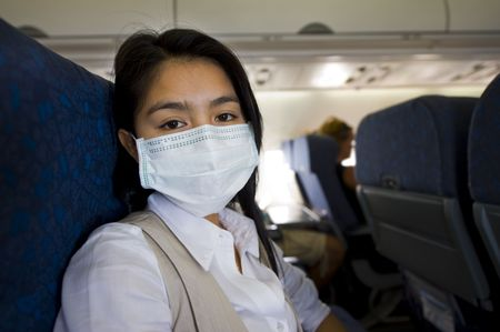 dust mask: woman with protective mask in an airplane Stock Photo