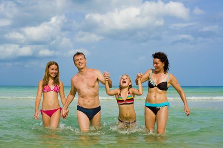 happy family walking in the sea holding each others hands photo