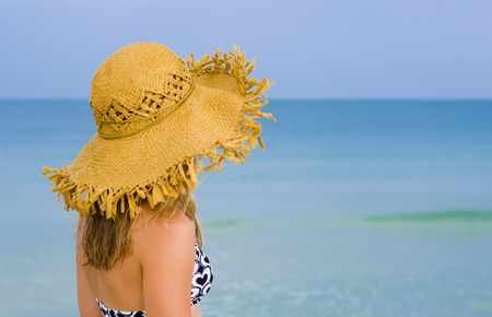 young blond woman with hat watching the sea photo