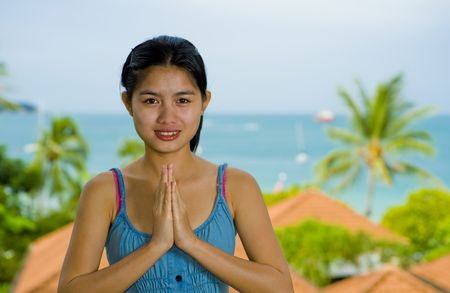 beautiful young asian woman with welcome expression in front of the sea photo