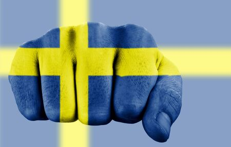 fist with swedish flag on blurred background photo