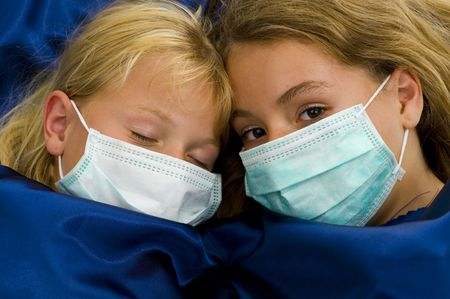 protective: two girls with protective masks sick in bed Stock Photo