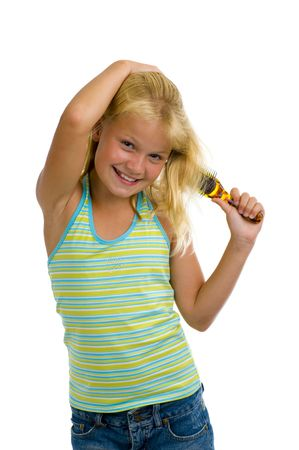 preteens girl: cute blond girl brushing her hair, isolated on white Stock Photo