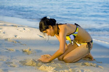 beautiful young woman playing with the sand photo