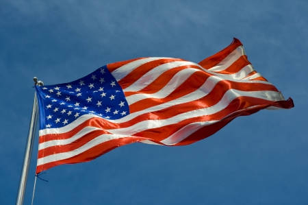 us flag on a pole against blue sky