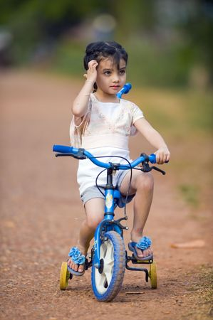 training wheels: cute thai-indian girl riding her bike on a dirtroad