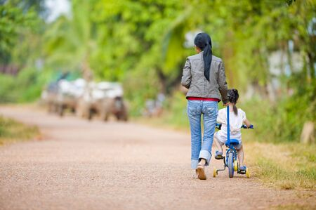 mother guiding her daughter on a bike