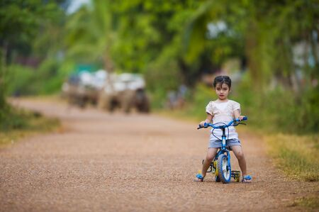 training wheels: cute thai-indian girl riding her bike on a dirt road. focus on the girl with a shallow depth of field and lot of free space.