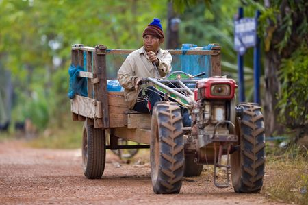 dirtroad: farmer on his small tractor on the countryside in thailand