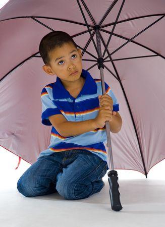 young cute boy kneeling under a huge umbrella photo