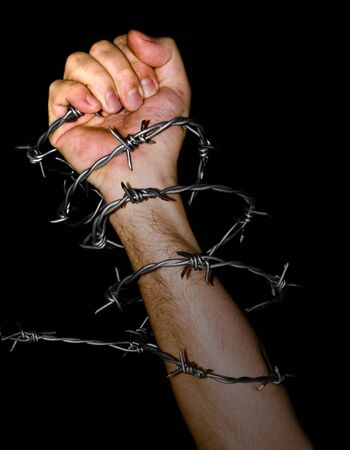 barbed wire fence: hand holding a barbed wire on black background