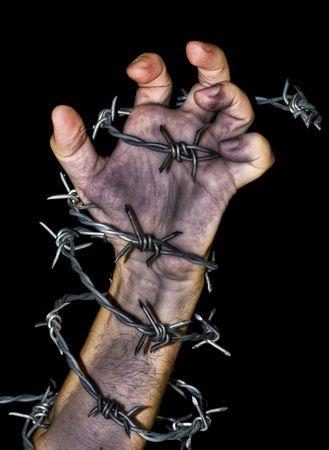 detenuti: sporco mano afferra un filo spinato su sfondo nero Archivio Fotografico