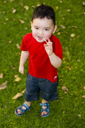 cute, small boy with lollipop in the park photo
